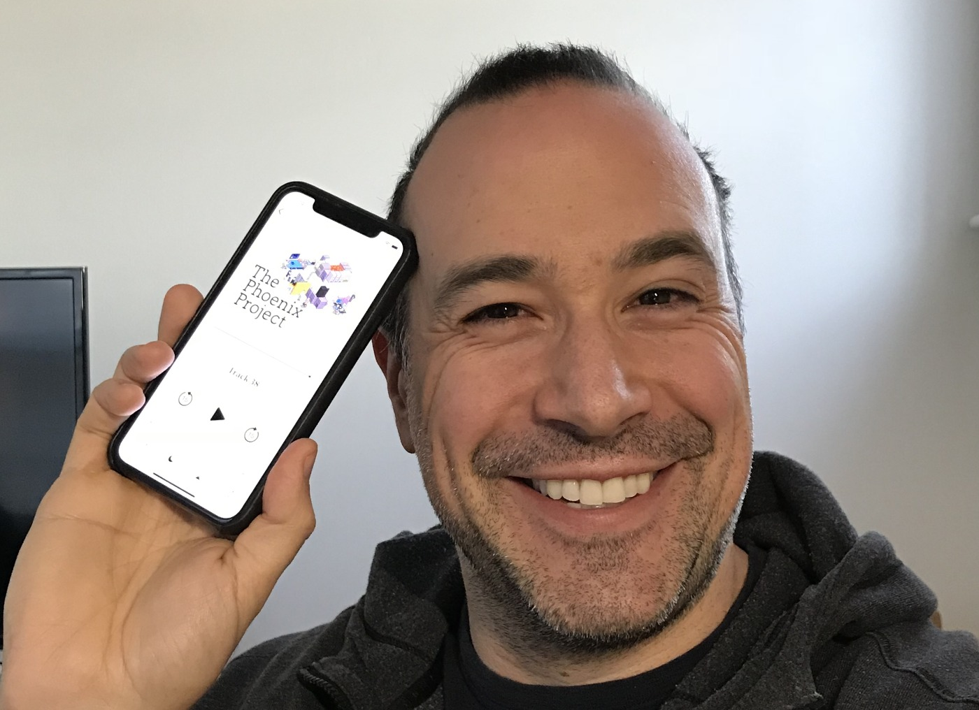 Ben Nadel holding an iPhone with iBooks showing The Phoenix Project.