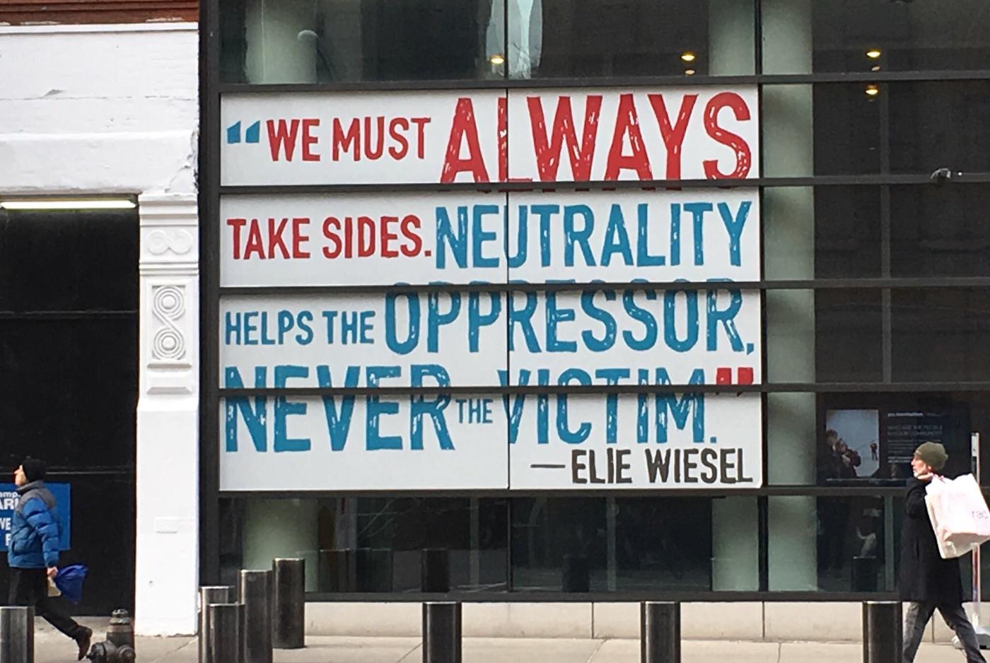 Poster in a window: We must always take sides. Neutrality helps the oppressor, never the victim. Elie Wiesel.